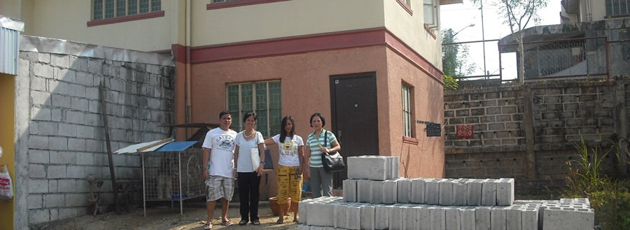 Filipino family with concrete block house